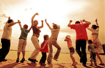 a group of people jump and raise their hands with the sunset in the background
